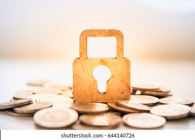 Money and Security Concept. Wooden master key lock icon on pile of coins.
