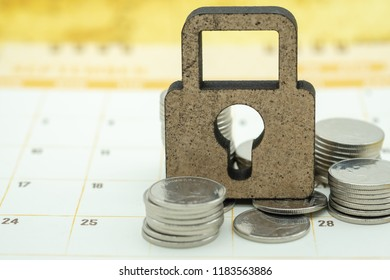 Money security, planning and business concept. Close up of Wooden master key lock icon on calendar with stack of coins.
