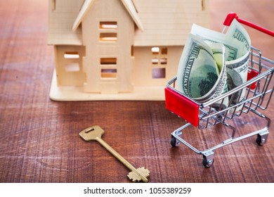 Money in a shop trolley, key and house on a wooden background.. Buying a property.