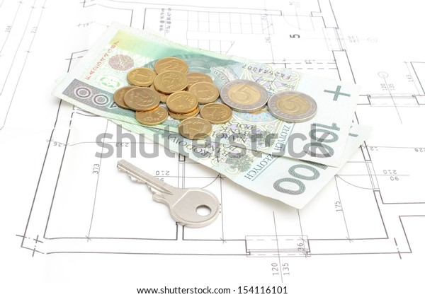 Money and silver key lying on construction drawing of house