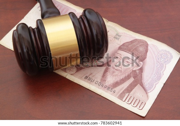 Money of South Korea and  gavel on brown table