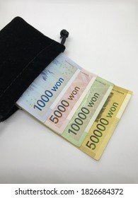 Money; South Korean Won (KRW) banknote inside pouch bag on white background. - Business, Finance and Economy Concept.