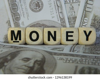 Money spelled out using gaming blocks on an American currency background