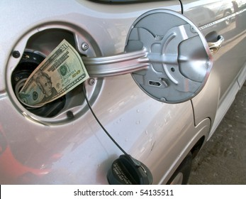Money sticking out of automobile fuel tank opening signifying and illustrating the high cost of gas.