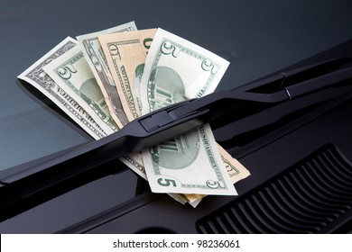 Money stuck under a windshield wiper symbolizing car expenses