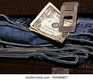 Money and a suitcase with jeans