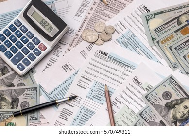 money, tax form, calculator and pen on desk.