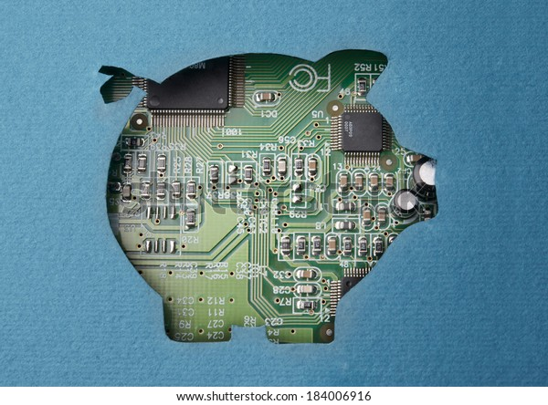 Money and technology. Cardboard piggy bank cutout revealing circuit board content