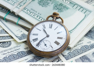 money and time concept - antique  pocket watch on pile of american dollars