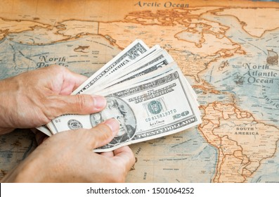 Money for travel Hand holding US. dollar with vintage map