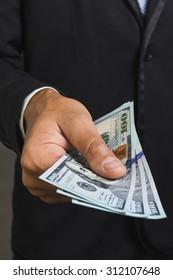 Money US dollars in businessman's hands