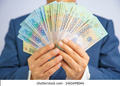 Money in Vietnam hold on hand business man wearing a blue suit (Socialist Republic Of Vietnam), Dong, VND, Pay, exchange money vietnamese on white background.