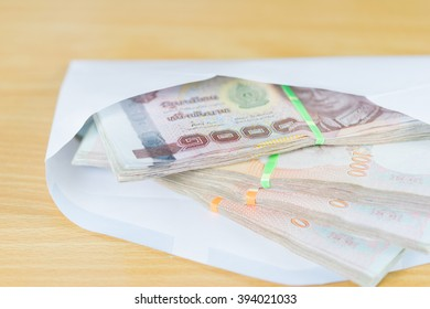 money in white envelope for someone on wood table