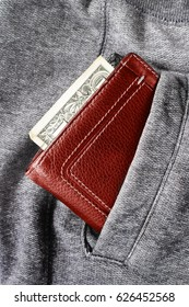 Money is written out with one dollar and a  burgundy purse on the background of gray trousers