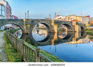 Monforte de Lemos, Galicia, Spain. The old (Roman) bridge and its beautiful reflection in the river Kabe at sunrise.