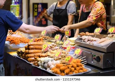 Mong Kok, Hong Kong : 03-August-2018 : Tourist is buying various of food at the street market at night in Mong Kok, Hong Kong.