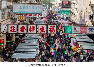 MONG KOK, HONG KONG - DEC 22, 2013: Crowded market stalls in Ladies' Market on Tung Choi Street in Hong Kong. It stretches one-kilometre with over 100 stalls of clothing, accessories and souvenirs.