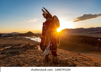 Mongolia shaman holding drum doing authentic ritual of summoning spirits.sunset moment with lens flare