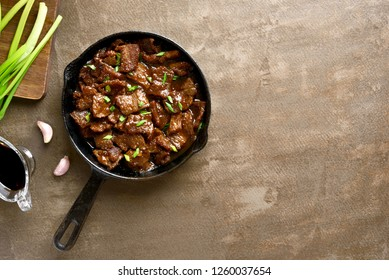 Mongolian beef, pieces of beef stewed in soy sauce with spices in asian style on brown background with copy space. Top view, flat lay