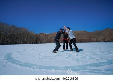 Mongolian boys wrestling on the frozen river Terelj, Tuv, Mongolia.
