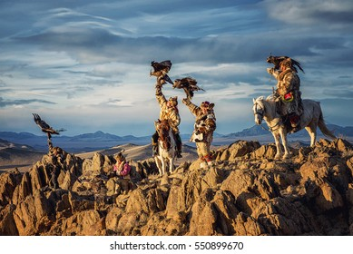 Mongolian eagle Hunters in traditionally wearing typical Mongolian Fox dress culture of Mongolia on Altai Mountain background at Ba-yan UiGII, MONGOLIA