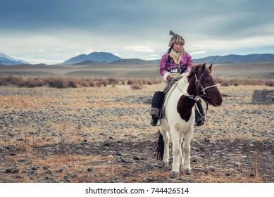 Mongolian eagle Hunters in traditionally wearing typical Mongolian Fox dress culture of Mongolia on Altai Mountain Background at Ba-yan UiGII, MONGOLIA