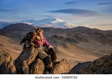 Mongolian Gilr eagle Hunters in traditionally wearing typical Mongolian Fox dress culture of Mongolia on Altai Mountain background at Ba-yan UiGII, MONGOLIA