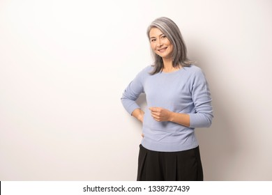 Mongolian Gray Haired Woman on a White Background. A Woman's Smile Emphasizes Her Elegance. She is Wearing a Blue Blouse and Black Pants. Mongolian Beauty Concept. Close Up Shoot.