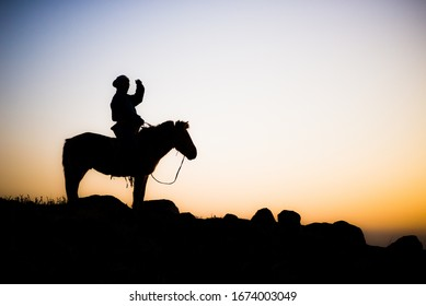 Mongolian Horse Rider In The Sunrise Morning By The Cliff Of The Mountain With Ger In Gobi Desert In Mongolia