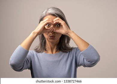 Mongolian Mature Woman Holds Hands As if Looking Through Binoculars. The Woman Has Gray Hair. Her Face Looks Funny. She Opened Her Eyes Wide with Surprise. Behind the Woman is a Gray Background. Close