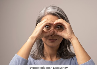 Mongolian Mature Woman Holds Hands As if Looking Through Binoculars. The Head of the Woman is Covered with Gray Hair. Her Eyes are Big and Brown. Close Up Shoot.