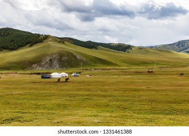 Mongolian steppe with grassland, yurts, horses and sky with clouds