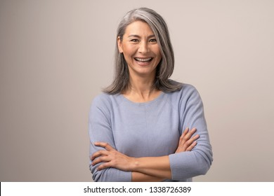 Mongolian Woman with Gray Hair on a Gray Background. She Smiles Broadly. Her Arms are Crossed Before Her. Close Up Shoot.
