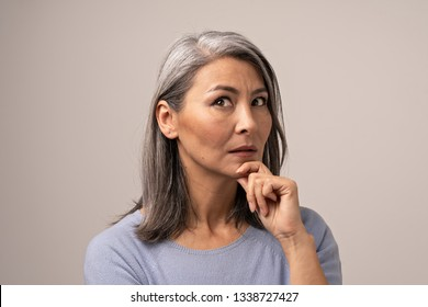 Mongolian-Looking Woman with Gray Hair on a Gray Background. Her Face Looks Thoughtful. The Woman s Gaze is Directed Upwards. Her Hand Props Her Chin. Close Up Shoot.