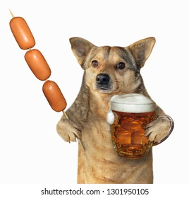 The mongrel dog is holding a mug of beer and a sausage skewer. Isolated. White background.