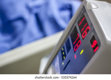Monitor on Trolley with Blood Pressure Cuff and Thermometer on hospital background.