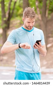 Monitoring and boosting his training. Sportsman tracking his training with fitbit and smartphone. Fit man paring smartwatch with mobile device for training. Physical training and sports.