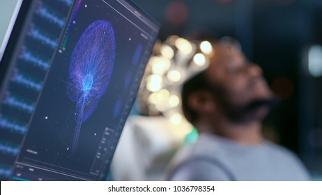 Monitors Show EEG Reading and Graphical Brain Model. In the Background Laboratory Man Wearing Brainwave Scanning Headset Sits in a Chair with Closed Eyes. In the Modern Brain Study Research Laboratory