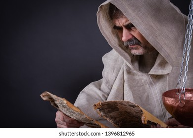 A monk alchemist is engaged in science, reading ancient manuscripts on birch bark