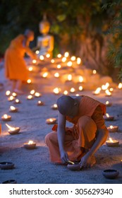 A monk, Asalha Puja Day - July 30 : Unidentified monks put candles on floor around image buddha in Asalha Puja Day on July 30, 2015 at Phan Tao temple in Chiang Mai, Thailand