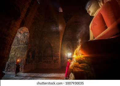 Monk in Bagan old town pray a buddha statue with candle, bagan city, Myanmar