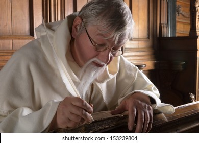 Monk with beard writing with a feather in an old book