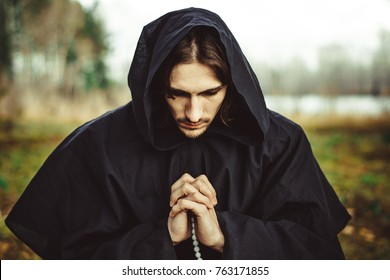 monks in black robes with nude women