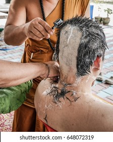 Monk cutting hair and shaving head during ordination of future buddhist monk