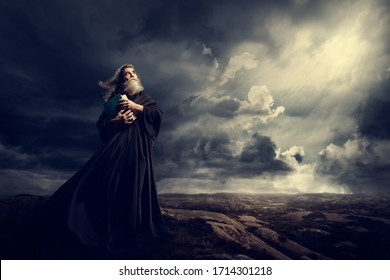 Monk Holding Bible Looking Up to God Sky Light, Old Priest in Black Robe in Storm Mountains - Shutterstock ID 1714301218