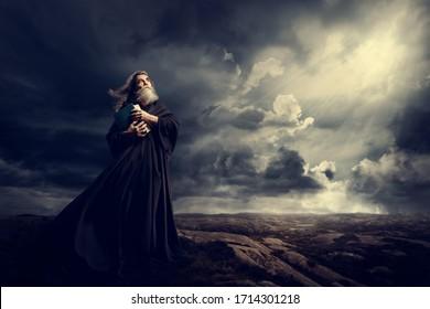 Monk Holding Bibel Blick auf Gotthard Himmellicht, Alter Priester in Schwarzer Robe im Sturmgebirge