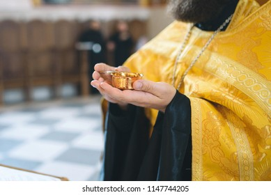 monk holding golden cup with wine at wedding ceremony