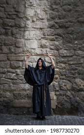 The monk holds his staff high against the textured stone wall, the light descending on him from above. Concept: prayer and magic, descent of the spirit, God's protection and healing.
