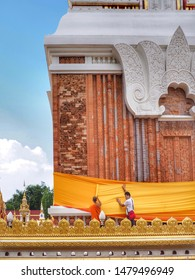 The monk and the man hold robe for wrap around church , made merit in beginning of Buddhist Lent , Buddhist tradition, at Wat Phra That Phanom in Nakhon Phanom province, Thailand , on 29 July 2019