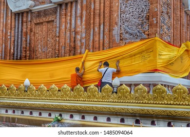 The monk and the man hold monk robe for wrap around church , in beginning of Buddhist Lent , Buddhist tradition, at Wat Phra That Phanom in Nakhon Phanom province, Thailand , on 29 July 2019